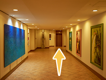 廊下の奥のエレベーターへ